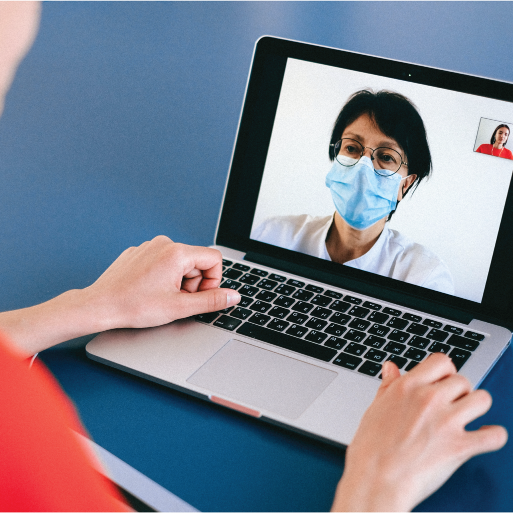 A women in a red shirt is video conferencing using her laptop with a patient in a medical mask.