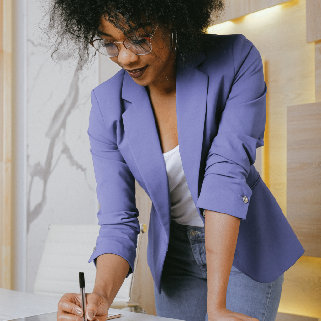 A woman wearing a business blazer is standing and writing in pen on a pad of paper.