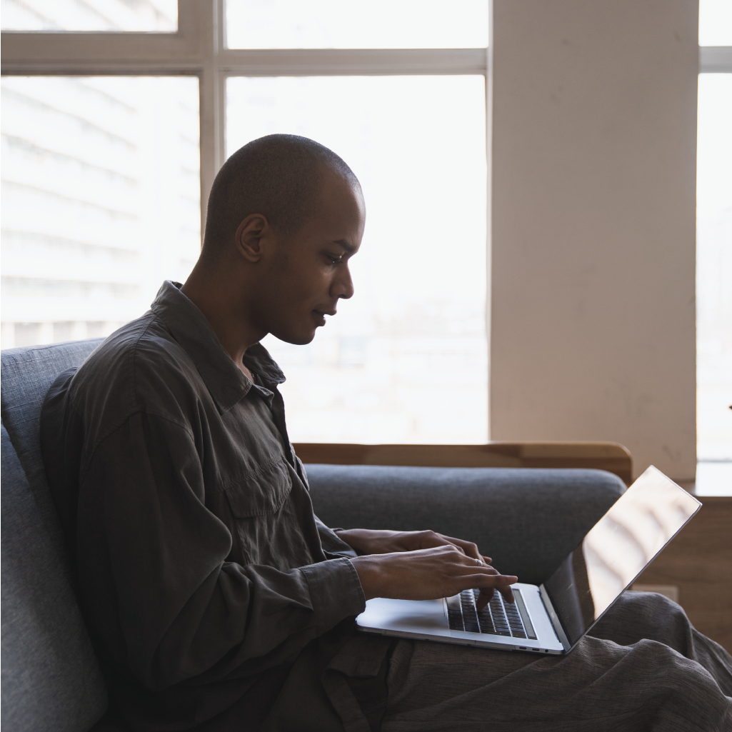 A man sitting on a couch typing on a laptop computer.